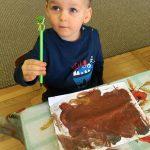 Chłopiec siedzący przy stoliku pokazujący kredkę. Przed nim, na stole znajduje się pomalowany farbami obrazek przedstawiający misia.