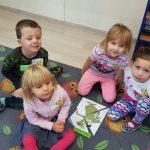 Czworo dzieci siedzących na dywanie. Pomiędzy nimi znajduje się obrazek przedstawiających misia złożonego z puzzli.
