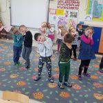 Grupa dzieci stojących na dywanie ze złożonymi przy twarzy rękami.