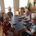 Sześcioro dzieci siedzących przy stoliku, mających przed sobą batoniki i lizaki.