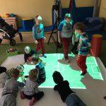 Grupa dzieci bawiących się na dywanie interaktywnym. Obok nich siedząca na dywanie nauczycielka.