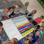 Trzynaścioro dzieci siedzących w kole na dywanie. W środku znajduje się mata, na której stoją kolorowe kubki.