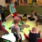 Grupa dzieci bawiących się na dywanie interaktywnym.