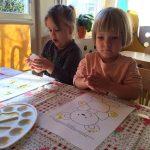 Dwoje dzieci siedzących przy stoliku i malujacych farbami obrazki przedstawiających misie.