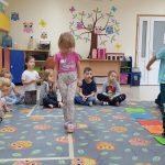 Dziewczynka stąpająca po przyklejonej na dywanie taśmie stopa za stopą. Obok niej chłopiec stojący na zielonej kartce, położonej na dywanie. Z tyłu dzieci siedzące na dywanie po turecku.