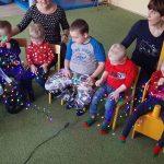 Grupa dzieci i 2 Panie siedzą na krzesłach. w rękach trzymaja kolorowej lampki choinkowe.