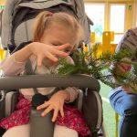 Dziewczynka trzyma w ręce gałązkę świerku