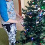 Chłopiec powiesza bombkę na choince.