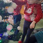 Chłopiec i dziewczynka powieszają bombkę na choinkę.
