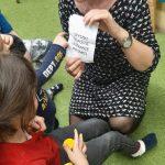 Pani trzyma w ręce kartkę z napisem SZYSZKI i pokazuje ją dzieciom.