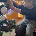 Chłopiec powiesza bombkę na choinkę.