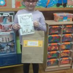 Uśmiechnięta dziewczynka w okularach trzyma w rękach dyplom i papierową torbę.
