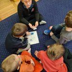 Pięcioro dzieci siedzi w małym kole. Po środku na dywanie leży kartka z układanką.