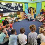 Dzieci siedzą na dywanie w kole. Po środku jest nayczucielka, która pokazuje coś dziecku.