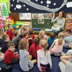 Dzieci siedzą przed tablicą z obrazkami. patrzą się na Panią nauczycielkę, która trzyma w ręce kostkę masła.