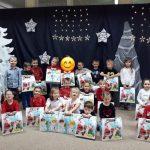 Grupa dzieci stojących na dywanie, trzymających świąteczne prezenty.