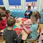 Kilkoro dzieci siedzi przy stoliku. Przed sobą mają tacę z wyciętym szablonem piernikowego ludzika. Trzymają w ręce pędzelek, a niektóre posypkę po pierników.