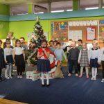 Grupa dzieci stoi w 2 rzędach trzymając się za ręce. Za nimi stoi ubrana choinka. jedna dziewczynka stoi przed resztą dzieci i trzyma w rękach mikrofon.