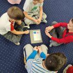 Czworo dzieci siedzi w małym kole. Po środku na dywanie leży kartka z układanką.