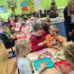 Grupa dzieci siedzi przy stoliku. Przed sobą mają tacę z wyciętym szablonem piernikowego ludzika. Trzymają w ręce pędzelek, a niektóre posypkę po pierników.