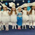 6 dziewczynek na granatowym tle stoi. Ubrane są w białe sukienki.