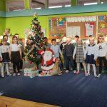 Grupa dzieci stoi w 2 rzędach trzymając się za ręce. Za nimi stoi ubrana choinka.