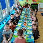 Grupa dzieci siedzi przy długim stole.