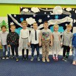 Grupa dzieci stoi na dywanie w eleganckim ubiorze.