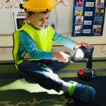 Chłopiec siedzący na dywanie i trzymający włączoną latarkę.