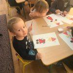 Dzieci siedzące przy stolikach, wykonujące prace plastyczne przedstawiając e Mikołaje.