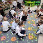 Grupa dzieci siedzących na dywanie wraz z trzema Paniami. Dzieci układają kształty z kolorowych pasków bibuły.