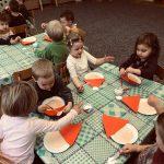 Dzieci siedzace przy stolikach i wykonujące prace plastyczne przedstawiające Mikołaje.