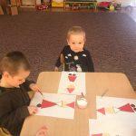 Dwoje dzieci siedzące przy stoliku, wykonujące prace plastyczne przedstawiające Mikołaje.