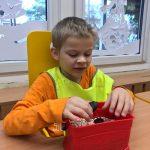 Chłopiec siedzący przy stoliku. Przed nim, na stoliku znajduje się pojemnik z bryłą węgla.