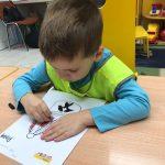 Chłopiec siedzący na krześle przy stoliku kolorujący rysunek czapki górnika.