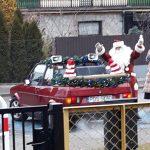 Mikołaj stojący obok samochodu. przed budynkiem przedszkola.
