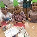 Trzy dziewczynki siedząc e przy stolikach i wykonujące prace plastyczne - mikołajkowe skarpety na prezenty.