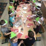 Grupa dzieci siedzących przy stolikach i wykonujących prace plastyczne- mikołajkowe skarpety na prezenty.