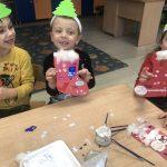 Troje dzieci siedzących przy stoliku i pokazujących prace plastyczne - mikołajkowe skarpety na prezenty.