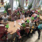 Grupa dzieci siedzących przy stolikach i pokazujących prace plastyczne - mikołajkowe skarpety na prezenty.