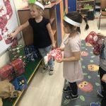 Dziewczynka przywieszająca mikołajkową skarpetę na prezenty na tablicę magnetyczną. Obok niej dziewczynka trzymająca w ręku pracę plastyczną - świąteczną skarpetę.