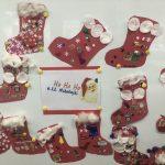 Prace plastyczne dzieci - mikołajkowe skarpety na prezenty wiszace na tablicy magnetycznej.