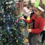 Dziewczynka zawieszająca bombkę na choince. Za nią dziewczynka trzymająca w ręku ozdobę świąteczną.