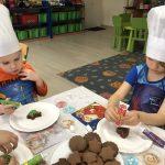 Dwoje dzieci siedzących przy stolikach i dekorujących pierniki.