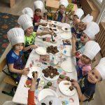 Grupa dzieci siedzących przy stolikach i dekorujących pierniki.