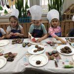 Troje dzieci siedzących przy stoliku i dekorujących pierniki.