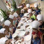 Grupa dzieci siedzących przy stolikach, jedzące udekorowane przez siebie pierniki