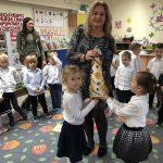Dwie dziewczynki wręczające Pani Dyrektor choinkę. Za nimi stoi grupa dzieci wraz z Panią.