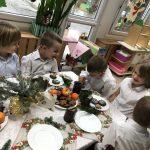 Pięcioro dzieci siedzących przy stole wigilijnym.