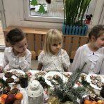 Troje dzieci siedzących przy stole wigilijnym.